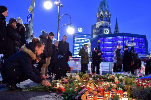 Grupo de gente colocando velas y flores en las calles de Berlín