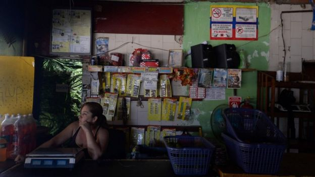 An employee of a supermarket waits during a power cut in Santa Teresa, Miranda State, Venezuela