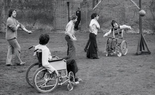 Five boys playing sports outside. Two are wheelchair users