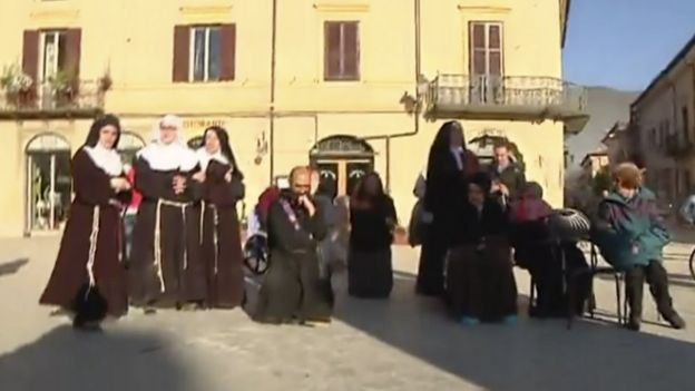 Priests and nuns join residents in the main square in Norcia after being evacuated from church on Sunday, 30 October 2016