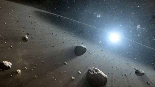 (ภาพจากฝีมือศิลปิน) แถบดาวเคราะห์น้อยและหินอวกาศรายล้อมอยู่รอบดาวเวกา (Vega)