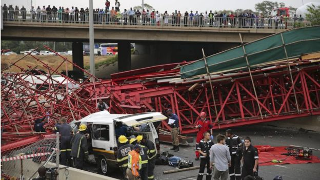 Paramedics try to free passengers trapped in a taxi after a bridge collapsed on the M1 highway