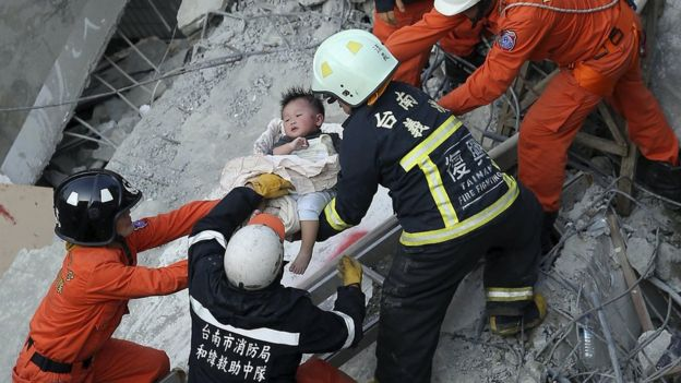 Rescue personnel help a child rescued at the site where a 17-storey apartment building collapsed during an earthquake in Tainan, southern Taiwan, February 6