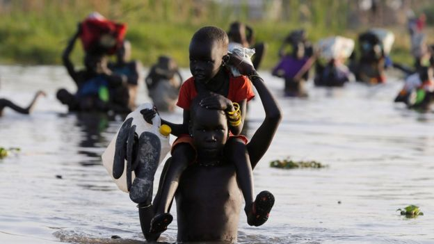 children cross water to register for aid