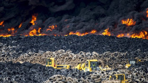 piles of intact tyres behind industrial diggers, with flames and smoke in the background, May 13 2016