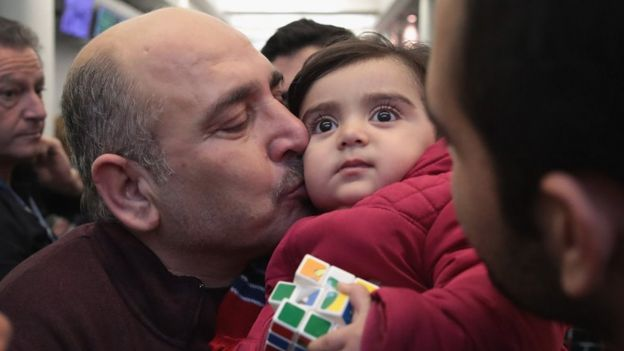 Khaled Haj Khalaf kisses his granddaughter Shams after she arrived with her mother and father at O'Hare Airport on a flight from Istanbul, Turkey on February 7, 2017 in Chicago, Illinois.