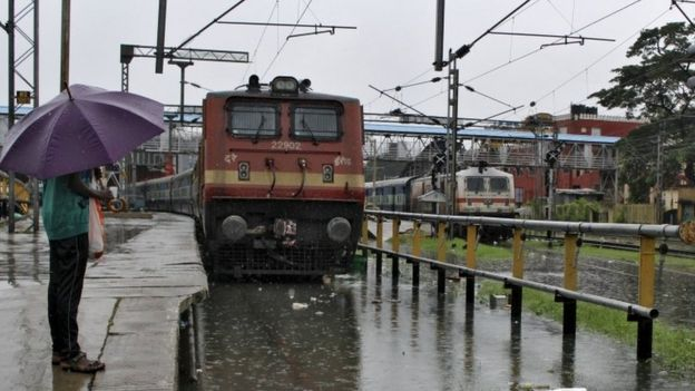 A man stands next to a flooded railway track as it rains in Chennai, India, December 2, 2015.