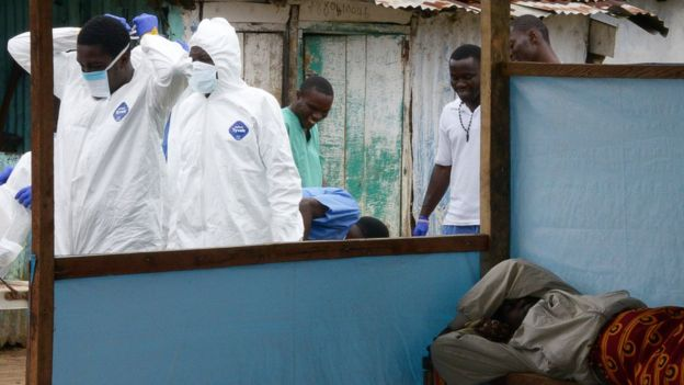 Ebola medical workers in protective suits walk past a sick women