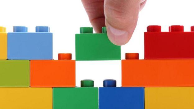 Una persona haciendo una construcción con piezas de Lego.