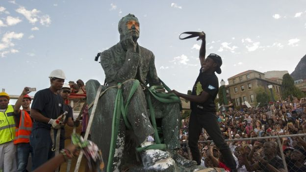 Students attack the defaced statue of British mining magnate and politician, Cecil John Rhodes, as it is removed by a crane from its position at the University of Cape Town on 9 April 2015
