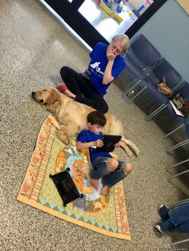 Madre de un niño con autismo lo ve recostado de un perro.
