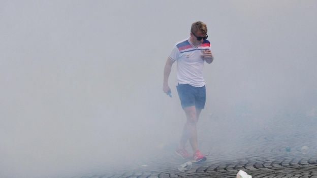 An England fan walks through tear gas in Marseille