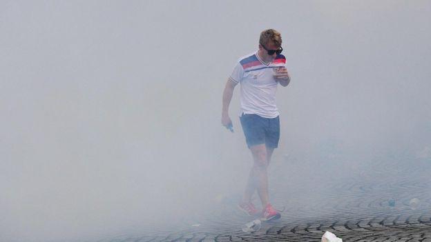 An England fan walks through tear gas in Marseille
