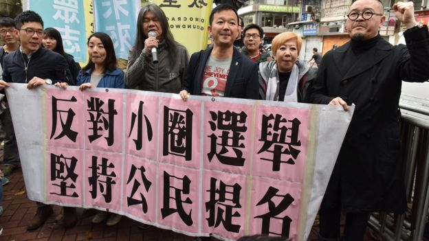 Lawmakers Nathan Law (L), Lau Siu-lai (2nd L), Leung Kwok-hung (3rd L) also known as 'Long Hair', Raymond Chan (3rd R) and Shiu Ka-chun (R) protest outside the venue of the Hong Kong chief executive election in Hong Kong on March 26, 2017.