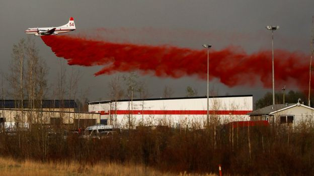 A plane drops fire retardant on the flames - 6 May