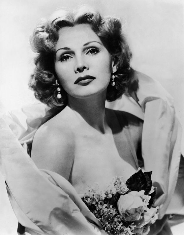 Portrait of Hungarian actress Zsa Zsa Gabor wearing a stole and carrying a bouquet of flowers, 1950s.