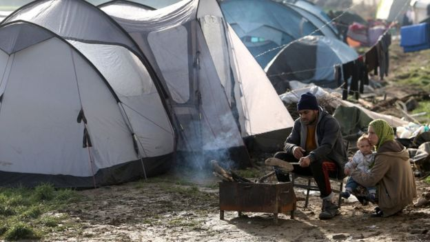 Migrants sit near a fire in a tent camp on 1 March, 2016 near the village of Idomeni as migrants and refugees walk to cross the Greece-Macedonia border.