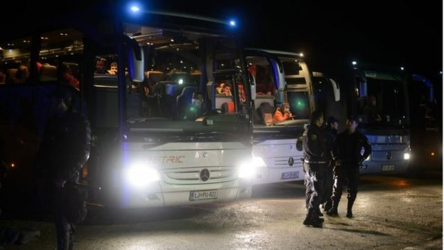 Buses carrying migrants and refugees who crossed the Croatian-Slovenian border wait to be dispatched near the town of Oresje, Slovenia, on 19 October 2015.