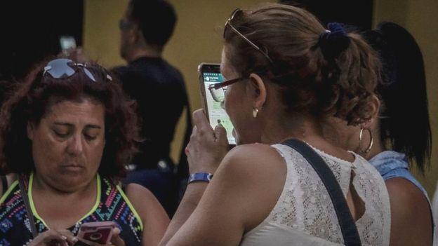 Pessoas usam wi-fi público para conectar seus aparelhos em uma rua em Havana