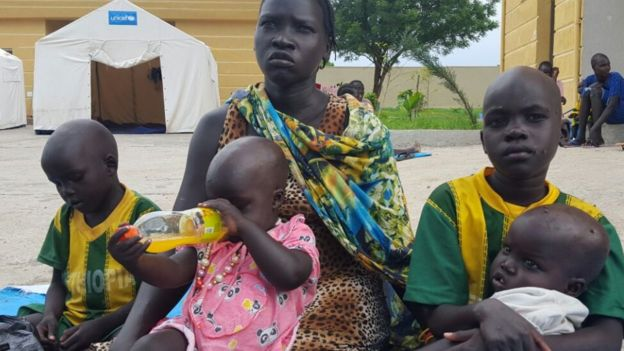 Nyamak Oukuch sits with her nieces and nephew in Gambella, Ethiopia