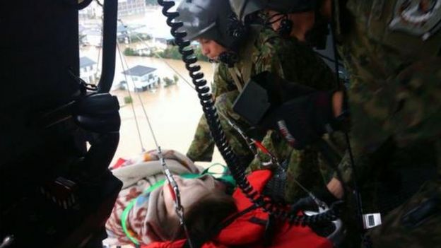 Japan floods  City of Joso hit by      unprecedented      rain   BBC News An injured person is lifted to safety by Japanese troops
