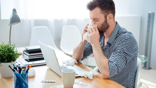 Un hombre en la oficina, resfriado, con pastillas y toallitas en el escritorio