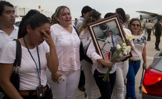 Familiares y amigos del piloto del avión de Lamia accidentado, Miguel Quiroga, cargan una fotografía suya durante su funeral.