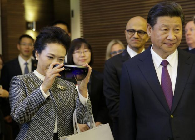 Peng Liyuan, left, stands next to her husband, Chinese President Xi Jinping as she examines Micosoft's HoloLens device during a tour of Microsoft's main campus in Redmond, Wash., Wednesday, 23 September 2015
