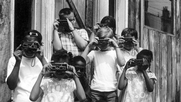 niños tomando fotografías con modelos antiguos de de Kodak.