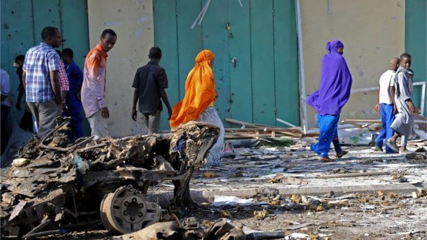People walk past the wreckage of a car at the site of a bomb blast near Makka al-Mukarama Road in Mogadishu on December 19, 2015.