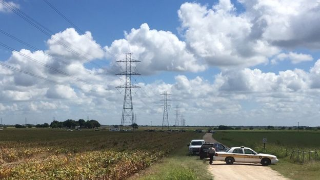 Police cars block access to the site where a hot air balloon crashed early Saturday, July 30, 2016, near Lockhart, Texas