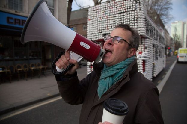Hugh Fearnley-Whittingstall standing with a megaphone in front of a bus covered cups