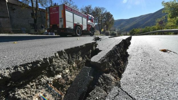 Fire engine passes near cracks on the road outside the center of Norcia