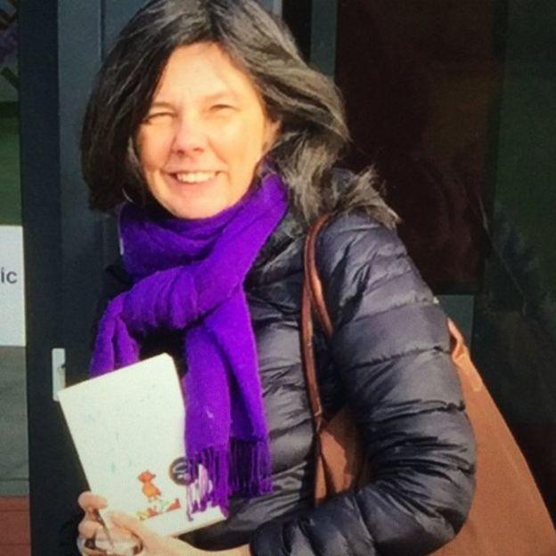 Bailey sonriendo con un libro en la mano.