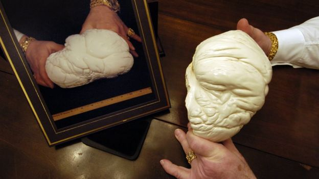 A man holds a replica of the Pearl of Lao Tzu, with the original seen in the photo, left, 2005