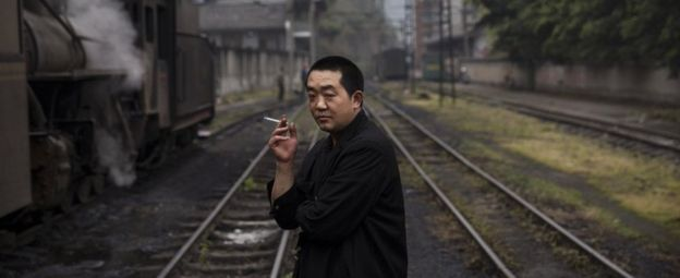 A railway engineer smokes as he waits next to a coal powered steam engine at a station in the town of Shixi , Sichuan Province