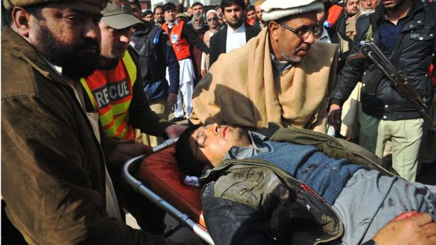 Rescuers take a man to hospital in Charsadda, Pakistan, 20 January