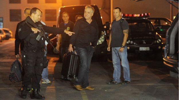 O empresário Carlinhos Cachoeira (ao centro), preso na Operação Saqueador, embarca na viatura da Polícia Federal após depoimento em 30/6/2016