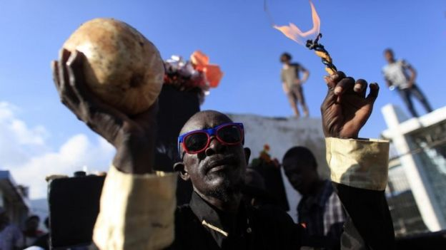 A voodoo believer participates in a ritual that pays tribute to Baron Samdi and the Gede family of spirits during Day of the Dead celebrations at the National Cemetery in Port-au-Prince, Haiti, Sunday, Nov. 1, 2015