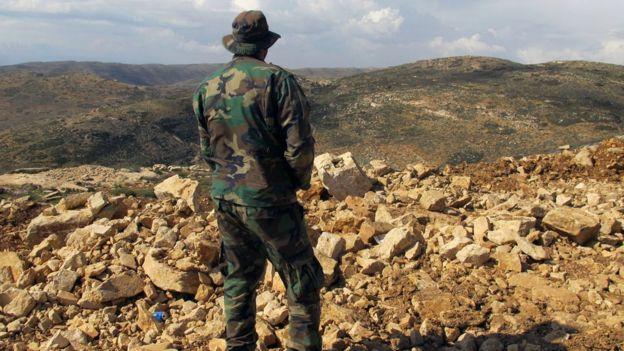 مقاتل من حزب الله ينظر إلى سوريا من وراء الحدود اللبنانية