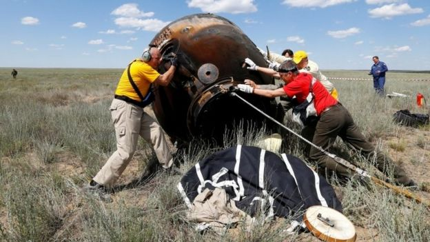 Search and rescue team members roll the Soyuz capsule over