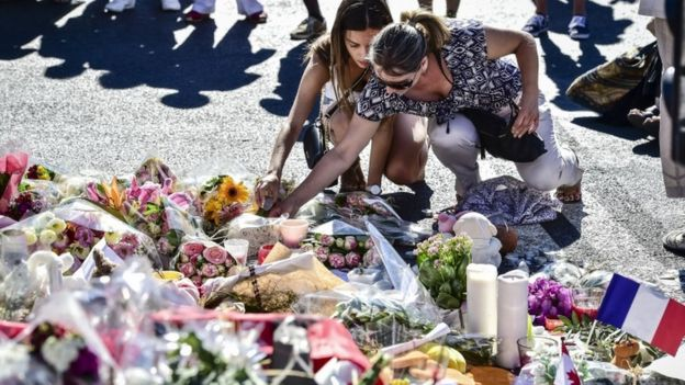 People placing candles among the tributes in Nice