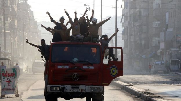 Rescue workers celebrate in Aleppo, 6 August
