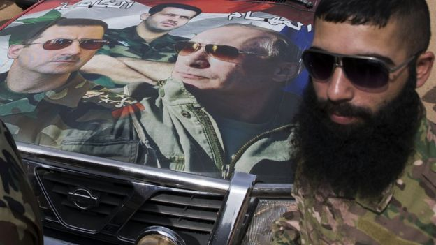 Syrian solder Hassan Muhammad stands near a car covered by a collage showing photos of faces of Russian President Vladimir Putin, right, Syrian President Bashar Assad, left, and a Syrian general, President's Assad brother, Maher Assad, centre, in Maarzaf, about 15 kilometres west of Hama, Syria, Wednesday, March 2, 2016