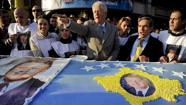 US former President Bill Clinton greets Kosovo Albanians as he stands in front of giant cake made for him during his visit to Pristina on 1 November 2009