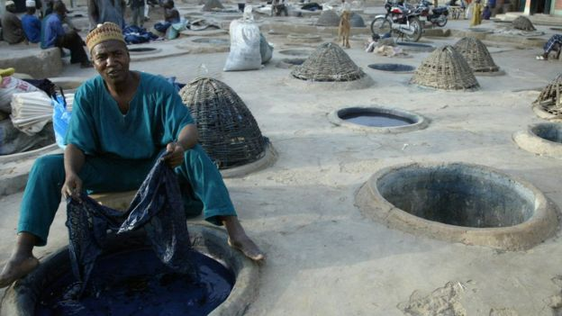 Man sat with fabric at Kano dye pit.