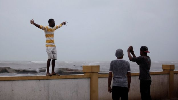 A man poses for a picture on a wall next to the sea ahead of Hurricane Matthew in Les Cayes, Haiti