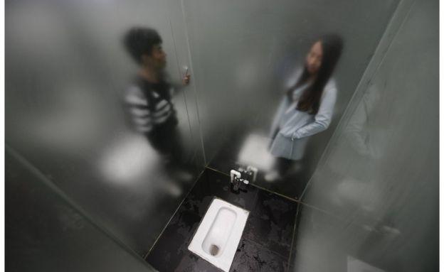Un hombre y una mujer en un cubículo cada uno.