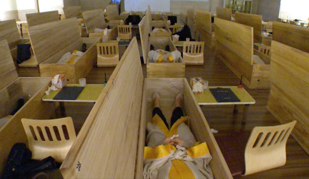 Employees lying in coffins