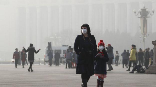 1月4日,两名头戴口罩的外国游客在北京天安门广场。北京正处于历史上最长的持续重度污染警报之中。